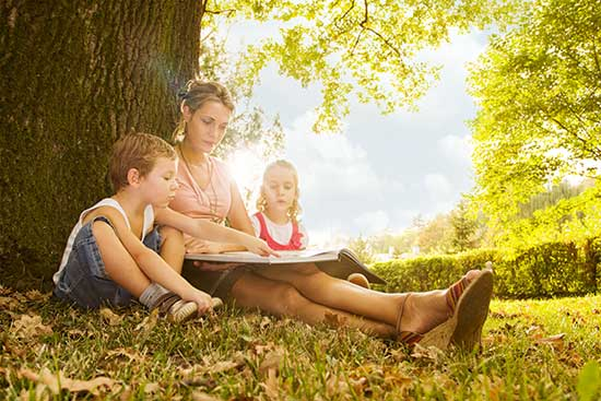 Woman reading book to children under tree