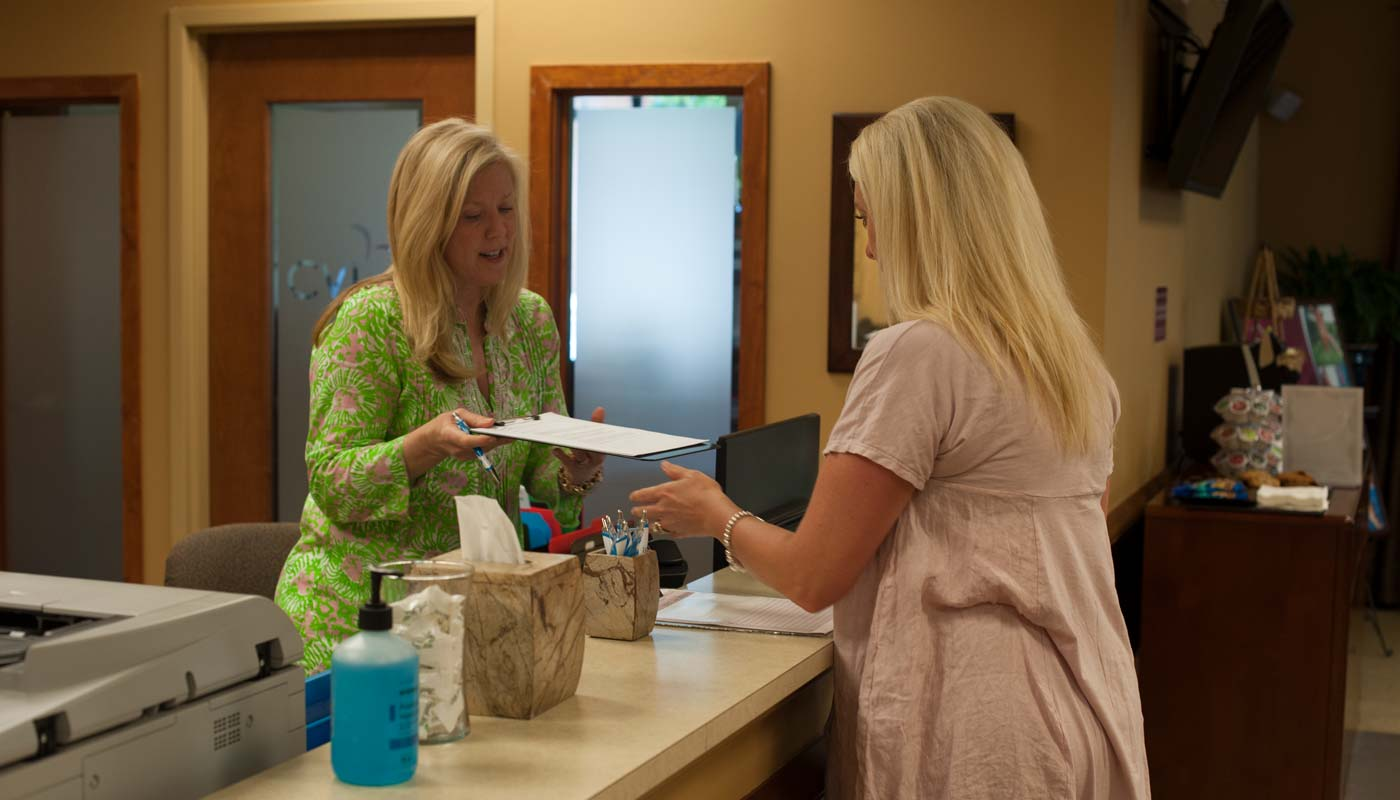 Nurse with patient at reception desk