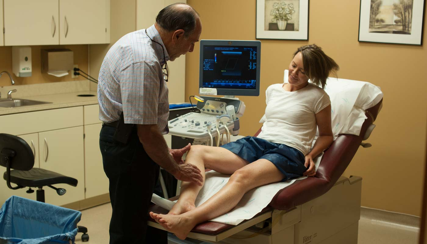 Doctor looking at legs of patient