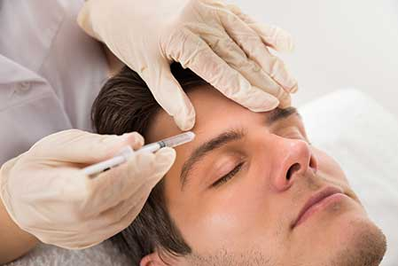 Man getting botox on his forehead