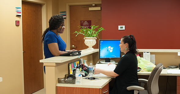 Nurses talking at reception desk